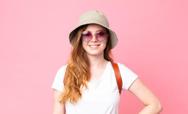 Czerwona głowa ładna kobieta turysta uśmiechnięta radośnie z ręką na biodrze i pewna siebie