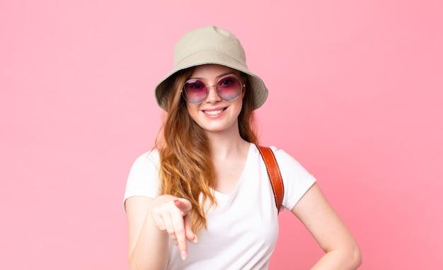 Czerwona głowa ładna kobieta turysta wskazując na aparat wybierający cię