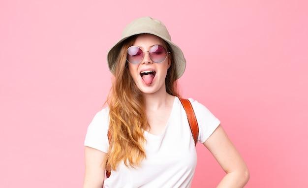 Czerwona głowa ładna kobieta turystka o wesołej i buntowniczej postawie, żartująca i wystawiająca język
