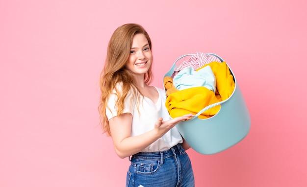 Czerwona głowa ładna kobieta uśmiecha się radośnie, czuje się szczęśliwa i pokazuje koncepcję i trzyma kosz do prania z ubraniami