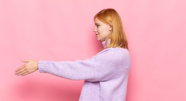 Czerwona głowa ładna kobieta uśmiecha się, wita i oferuje uścisk dłoni, aby zamknąć udaną transakcję, koncepcja współpracy