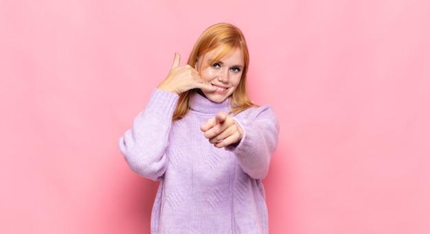 Czerwona głowa ładna kobieta uśmiechnięta radośnie i wskazująca podczas wykonywania połączenia gestem później, rozmawiając przez telefon