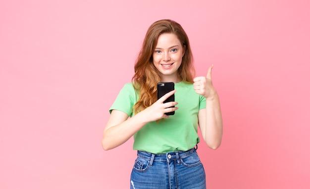 Czerwona głowa ładna kobieta używająca swojego smartfona