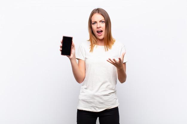 Czerwona głowa ładna kobieta wyglądająca na zdesperowaną i sfrustrowaną, zestresowaną, nieszczęśliwą i zirytowaną, krzyczącą i krzyczącą, trzymając smartfon