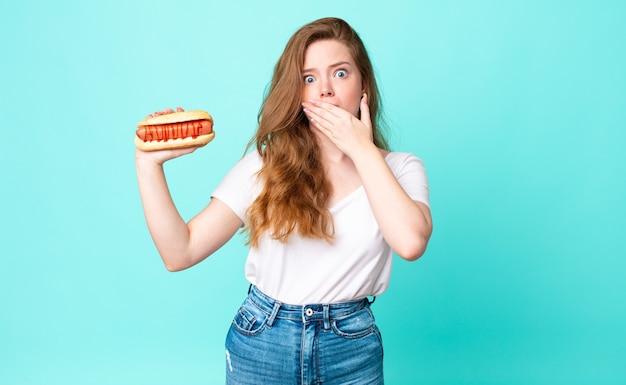 Czerwona głowa ładna kobieta zakrywająca usta dłońmi zszokowana i trzymająca hot doga
