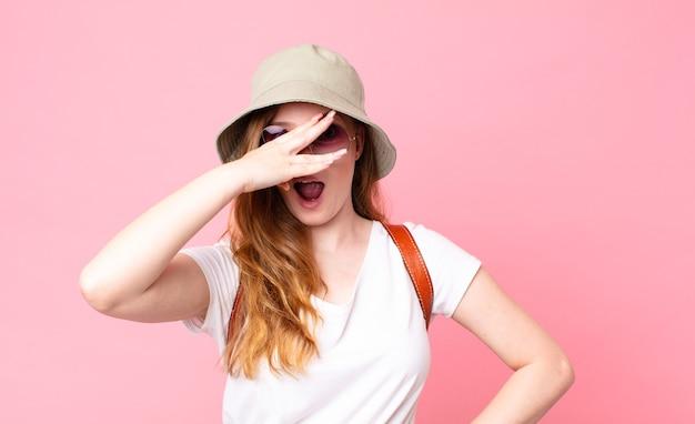 Czerwona głowa ładna turystka wyglądająca na zszokowaną, przestraszoną lub przerażoną, zakrywającą twarz dłonią