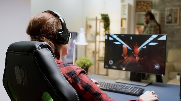 Czerwona głowa zdenerwowana kobieta straciła podczas grania w strzelanki na komputerze. kobieta siedzi na fotelu do gier.
