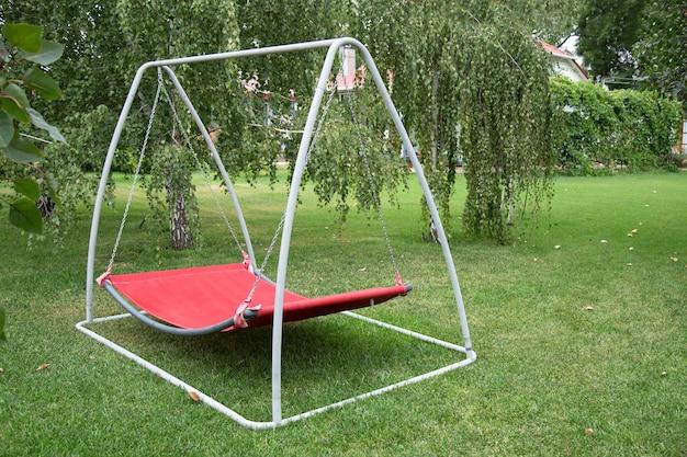 Czerwona huśtawka hamakowa w metalowej ramie z nikim na zielonym trawniku na podwórku. odpoczynek relaks relaks sam na hamaku huśtawka w letnim ogrodzie.