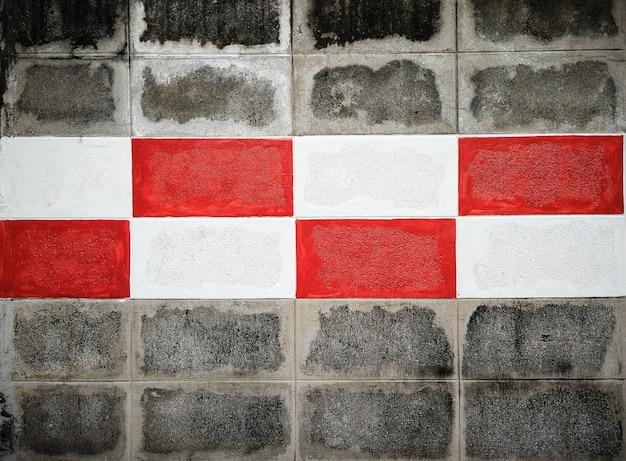 Czerwona i biała farba na ściennym ceglanym tle.