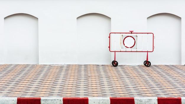 Czerwona i biała stalowa bariera na bruku