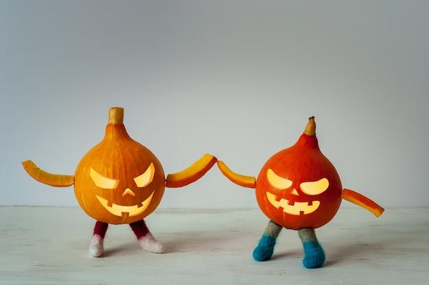 Czerwona i pomarańczowa dynia z halloweenową twarzą, nogami i rękami trzymając się za ręce. dwóch małych przyjaciół w filcowych butach. jasne tło z winiety. skopiuj miejsce.