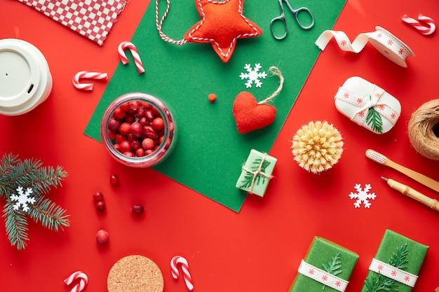Czerwona i zielona ściana xmas. modne, przyjazne dla środowiska ozdoby świąteczne i noworoczne bez marnotrawstwa oraz prezenty. geometryczne mieszkanie leżało z prezentami, żurawiną, bambusowym kubkiem do kawy i pędami cukierków.