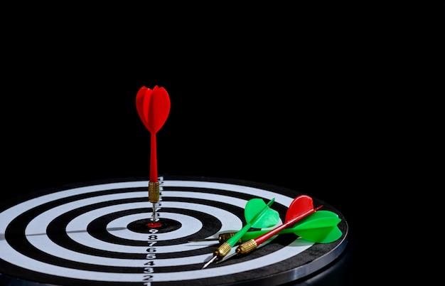 Czerwona i zielona strzałka strzałki uderzające w centrum celu to tablica do gry w rzutki na czarnej powierzchni