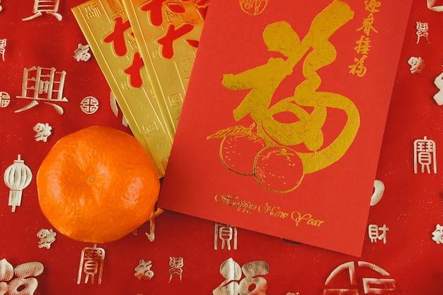 Czerwona i złota karta obok pomarańczowego
