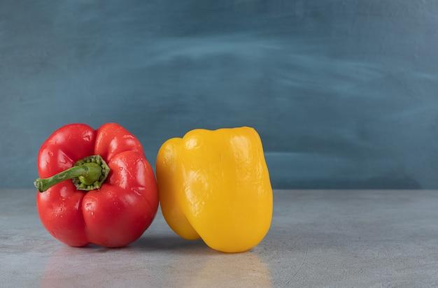 Czerwona i żółta papryka na szarym tle. zdjęcie wysokiej jakości