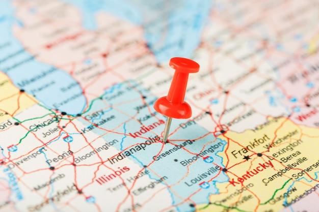 Czerwona igła biurowa na mapie usa, indiany i stolicy indianapolis. zbliżenie mapy strony chronionej oczekującymi zmianami indiana z czerwoną tacką