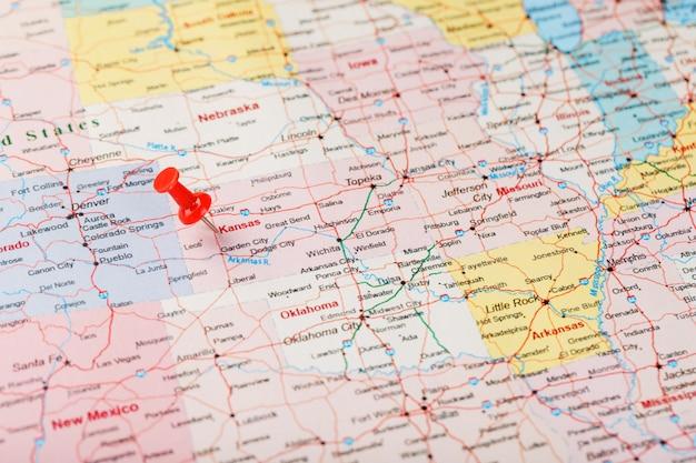 Czerwona igła biurowa na mapie usa, kansas i stolicy topeka. zamknij mapę kansas z czerwonym hals