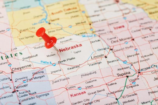 Czerwona igła biurowa na mapie usa, nebraski i stolicy lincoln. zamyka w górę mapy nebraska z czerwonym halsem
