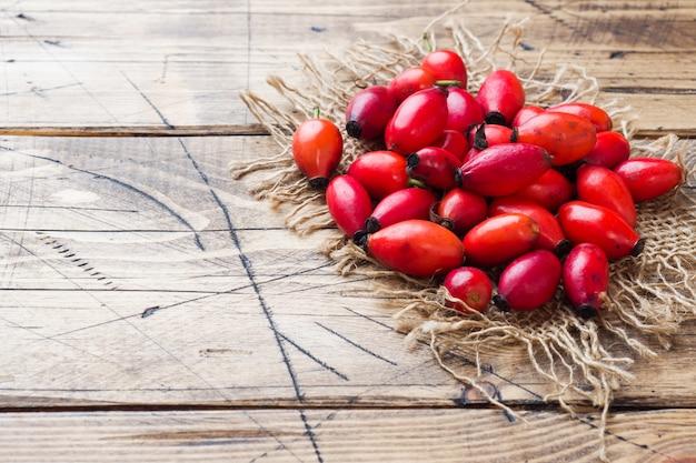 Czerwona jagody róży owoc na drewnie. skopiuj miejsce