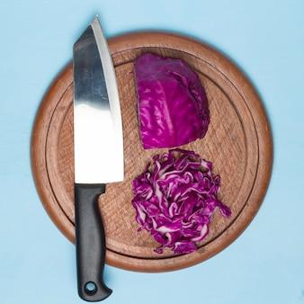 Czerwona kapusta wyciąć kawałek z nożem kuchennym na desce do krojenia drewna. na drewnie kuchennym