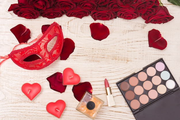 Czerwona karnawałowa maska, bukiet czerwonych róż, szminka, butelka perfum i cień do oczu na jasnym tle drewnianych.
