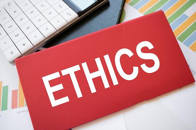 Czerwona kartka papieru z tekstem etyki, kalkulatorem i długopisem na pulpicie. pomysł na biznes