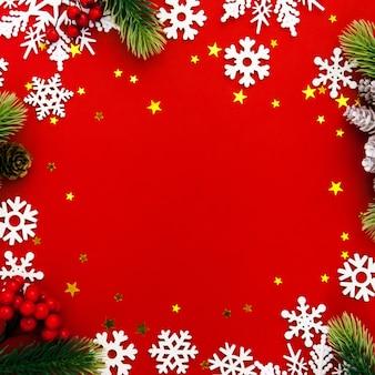 Czerwona kartka świąteczna w ramce z gałęzi jodły, płatków śniegu, jagód, gwiazd, ozdób świątecznych na czerwonym tle. makieta. płasko ułożona kwadratowa uprawa. widok z góry