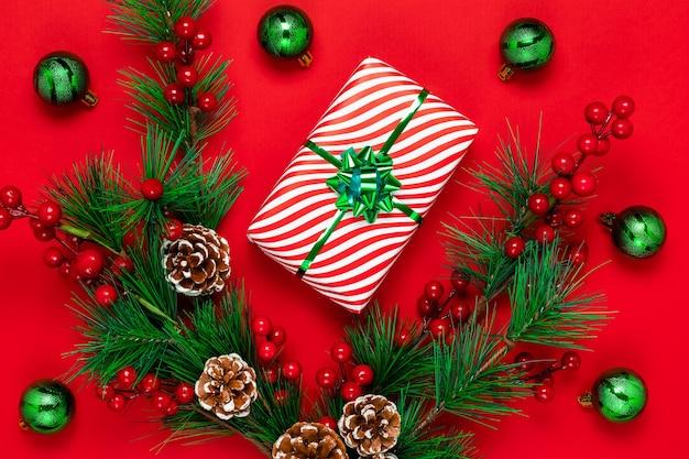 Czerwona kartka świąteczna z pudełkiem, gałęziami jodły, szyszkami, czerwonymi jagodami ostrokrzewu i zielonymi błyszczącymi kulkami. nowy rok tło z blichtr i świąteczny prezent. zimowa płaska kompozycja.