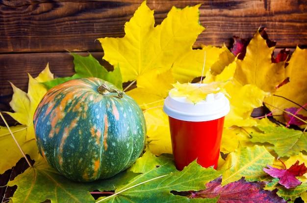 Czerwona kawa na wynos kubek z liśćmi marple i dynią