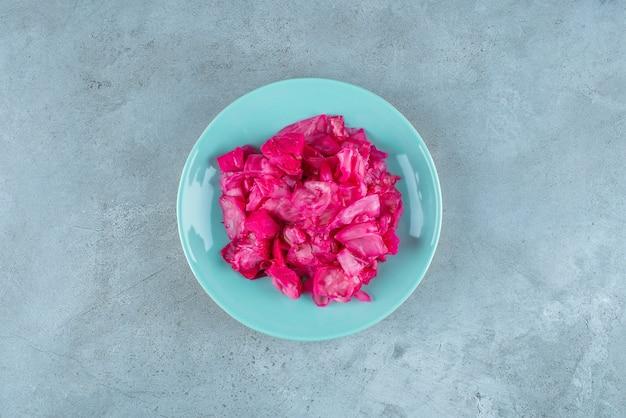 Czerwona kiszona kapusta na talerzu, na niebieskim stole.