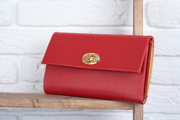 Czerwona kobieta s skórzana sprzęgło na drewnianej półce na białej ścianie w sklepie. idealna do codziennego, swobodnego wyglądu oraz do ładnej sukienki koktajlowej.