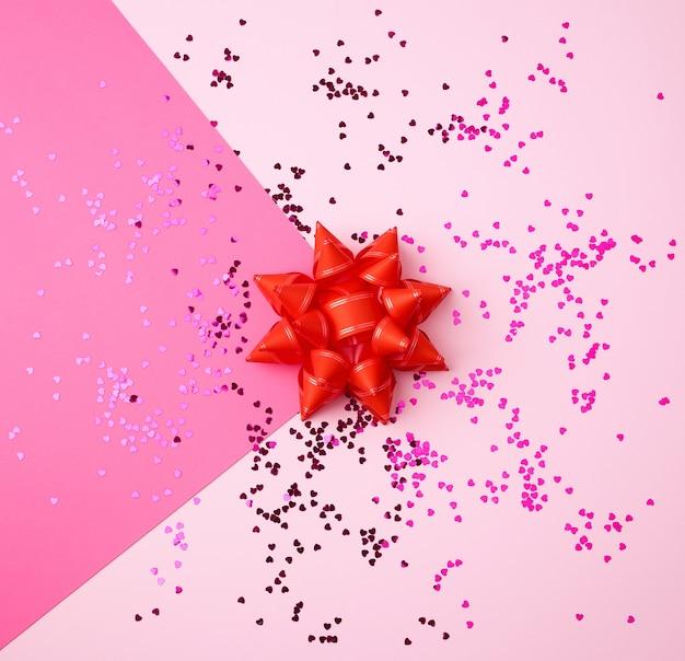Czerwona kokarda i błyszczące wielokolorowe okrągłe konfetti rozrzucone na różowym tle