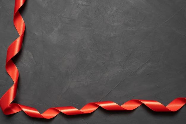 Czerwona kokarda satynowa tekstura na betonowym tle. skopiuj miejsce. baner