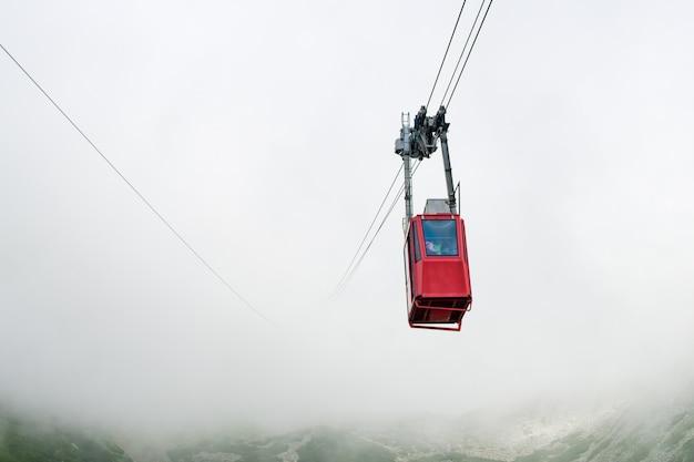 Czerwona kolejka linowa lub czerwona podwieszana kolejka linowa na łomnicki szczyt we mgle lub chmurach wysoka tatry słowacja