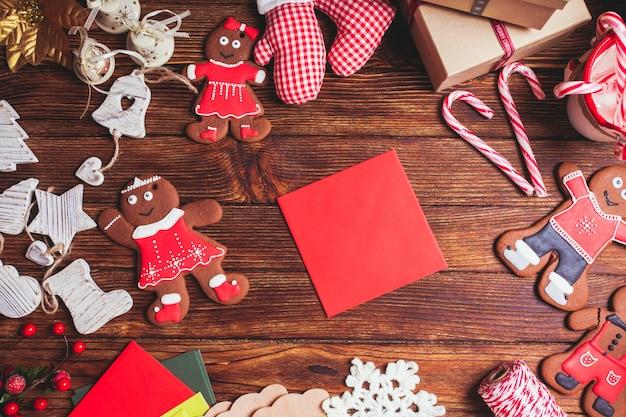 Czerwona koperta na stole, czekająca na kartkę z życzeniami świątecznymi