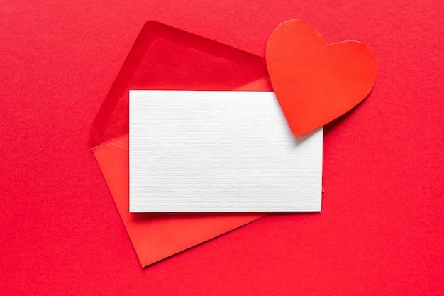 Czerwona koperta papierowa z czystego papieru i serca valentines na czerwonej powierzchni