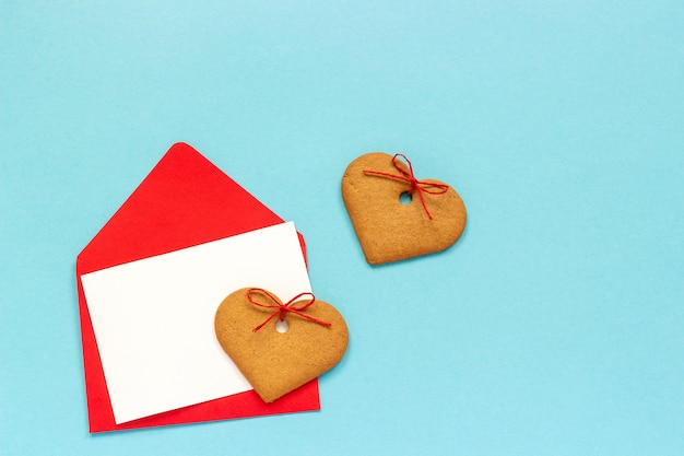 Czerwona koperta z pustą białą kartą dla teksta i kierowych kształtnych imbirowych ciastek