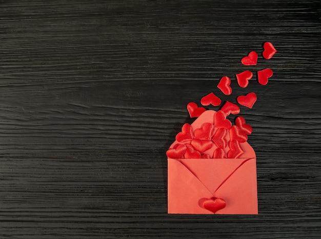Czerwona koperta z sercem na czarnym teksturowanym drewnianym