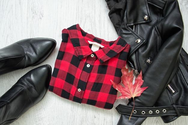 Czerwona koszula w kratę, czarna kurtka i liść klonu. modna koncepcja