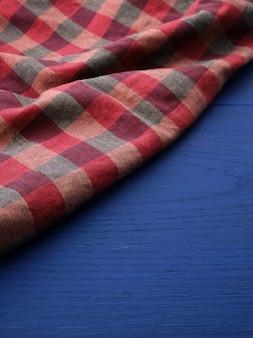 Czerwona kraciasta tkanina na niebieskim drewnianym