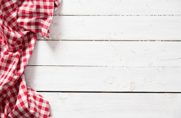 Czerwona kratka obrus kuchenny na drewnianym stole.