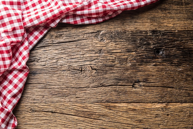 Czerwona kratka obrus kuchenny na rustykalnym drewnianym stole.