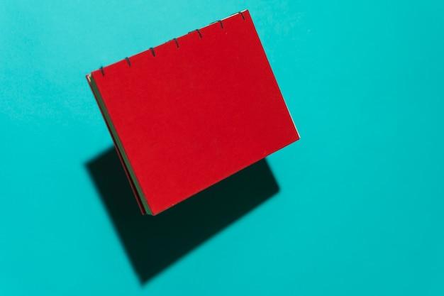 Czerwona książka na białym tle unosząca się czysta przed niebieskim tłem z miejscem na kopię tekstu