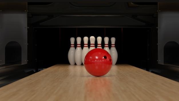 Czerwona kula do kręgli na drewnianym torze z szpilkami