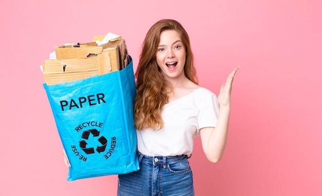 Czerwona ładna kobieta czuje się szczęśliwa i zdumiona czymś niewiarygodnym i trzyma papierową torbę z recyklingu