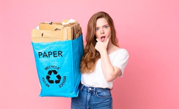 Czerwona ładna kobieta z szeroko otwartymi ustami i oczami, ręką na brodzie i trzymającą papierową torbę z recyklingu
