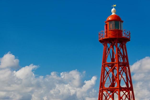 Czerwona latarnia morska na niebieskiego nieba tle