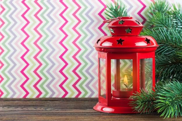 Czerwona latarnia z płonącą świecą na kolorowym tle z choinką.