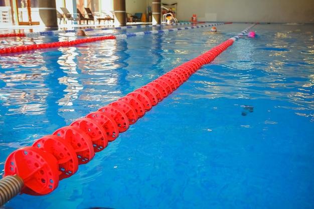 Czerwona linia oznaczona do przygotowywania zawodów pływackich. basen z oznaczonymi liniami. pusty basen bez ludzi z cichą stojącą wodą. sporty wodne w krytym basenie, kompleks sportowy.