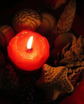 Czerwona mała płonąca świeca z dekoracją z ręcznie robionych muszelek